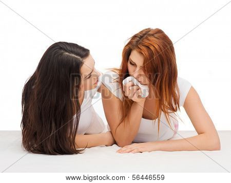 friendship and happy people concept - one teenage girl comforting another after break up