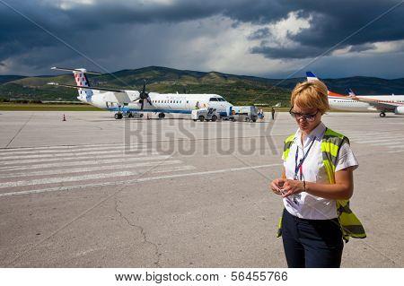 SPLIT, CROATIA - JUN 6: Airport staff standing on a runway of Split Airport during boarding on June 6, 2013 in Split, Croatia. Airport has very good connections to other European cities.