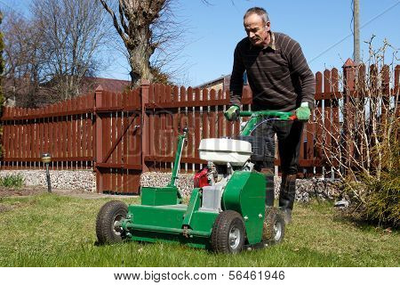 Spring work in garden. Man work with Man working with Lawn Aerator poster