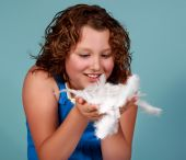 caucasian preteen girl holding some white feathers poster