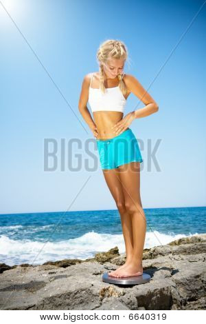 Beautiful smiling woman standing on a scale