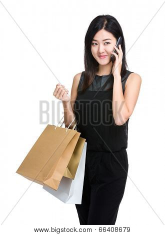 Asian woman holding shooping bag and listen mobile phone