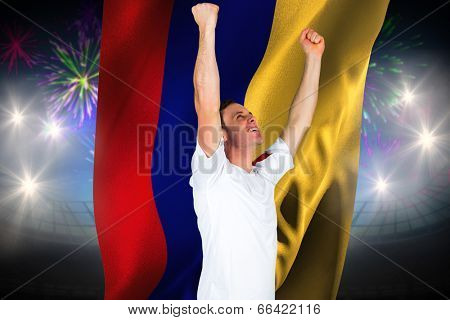 Cheering football fan in white against fireworks exploding over football stadium and colombia flag poster