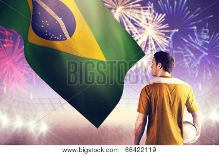 Football player in yellow holding ball against fireworks exploding over football stadium poster