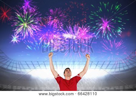 Excited football player cheering against fireworks exploding over football stadium poster