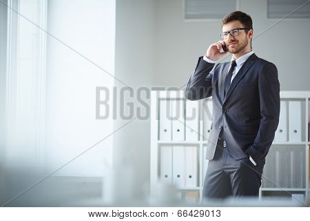 Handsome businessman in suit and eyeglasses speaking on the phone in office