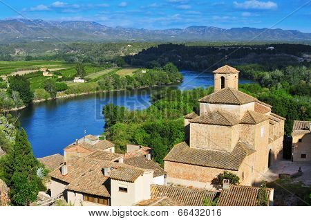 view of the old town of Miravet, Spain, and Ebro River with the Serra de Cardo mountain range in the background