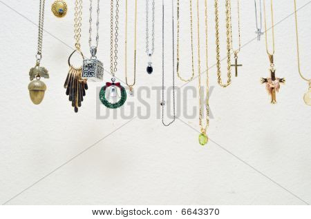 A bunch of various metal necklaces hanging up against a white wall. poster