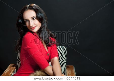 cute relaxing dark-haired girl in old-fashioned chair isolated