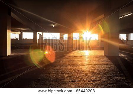 Sun peeking into large dark empty grunge parking structure interior.