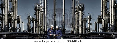two oil-workers with giant chemical refinery in background, fuel, oil and chemical industry