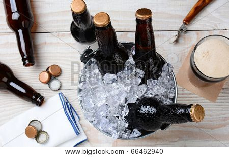 High angle shot of a glass of beer with a metal bucket with unopened bottles. The rustic wood table has empty bottles and caps and an bottle opener. Horizontal Format.