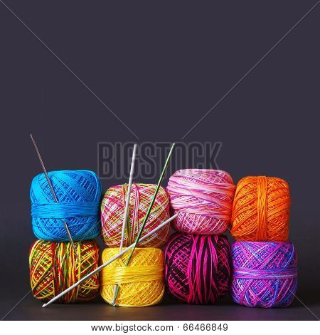 A tack of colorful yarn coils and needles over grey background