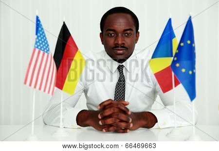 Serious african man sitting at the table in office