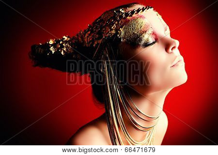 Art project: beautiful woman with golden make-up. Jewelry, make-up. Fashion. Over red background.
