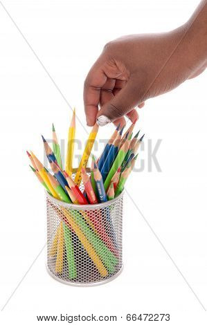 A hand reaching for coloured pencils