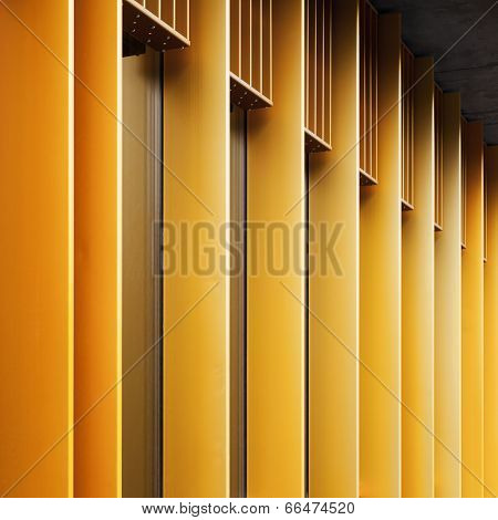 Abstract architecture fragment with yellow metal facade and windows poster