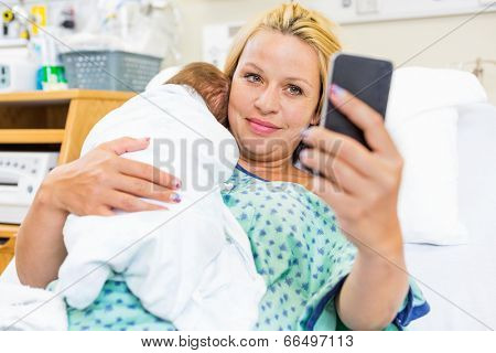 Mid adult female patient taking self portrait with newborn babygirl through smart phone in hospital room