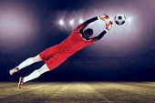 Goalkeeper in red jumping up against football pitch under spotlights poster
