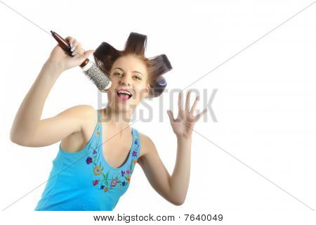 Young Beautiful Woman Singing To The Brush Microphone While Getting Her Hairstyle Done With Curlers