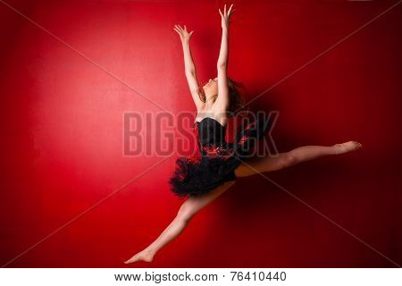 Young Ballerina Executing A Jump Against Bright Red Wall