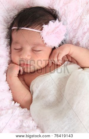 Newborn baby girl of Caucasian and Asian heritage wearing a head band.