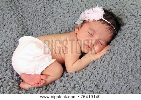 Newborn baby girl of Caucasian and Asian heritage, wearing a knitted hat.
