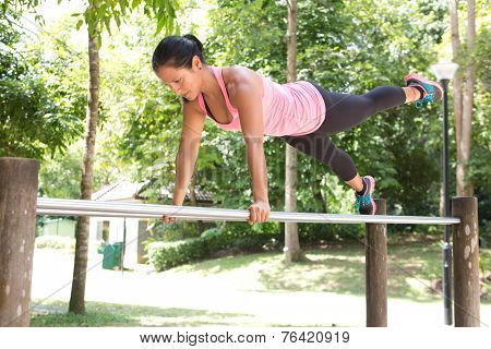 Beautiful woman doing dips exercise on balancing bar in park