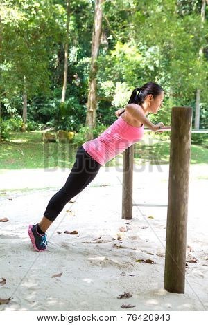 Strong woman doing push up exercise in park