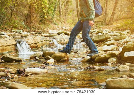 Hiker man with backpack crossing a river on stones in autumn forest view of legs. Hiking and leisure theme. Image with sunlight effect poster