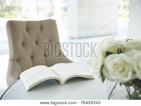 Book on Table with White Rose Flower in Living Room