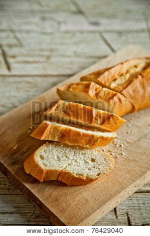 french bread baguette cut on wooden board