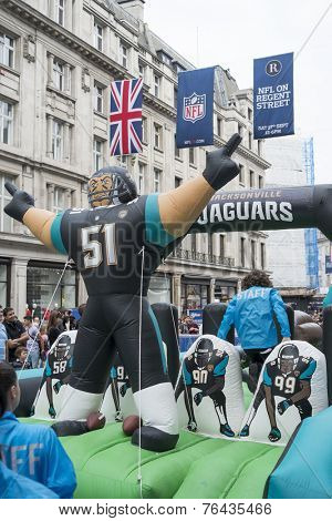LONDON UK - SEPTEMBER 27: Jacksonville Jaguars inflatable player and NFL flags in Regent Street. September 27 2014 in London. The street was closed to traffic to host NFL related games and events.