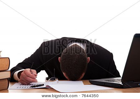 Stressed Young Man Sitting At A Table Among Books And Laptop On A White Background.