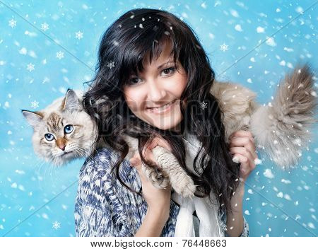 Charming young woman with siberian cat in snow poster