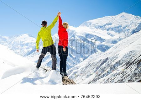 Couple Hiking Man And Woman Success In Winter Mountains