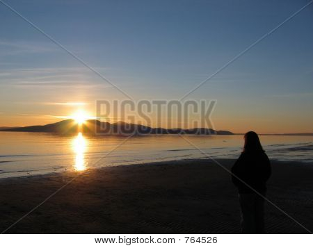Girl meditating and reflecting upon a beautiful sunset