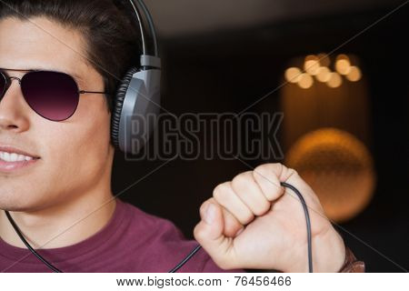 poster of Man in sunglasses listening to music with headphone at the nightclub