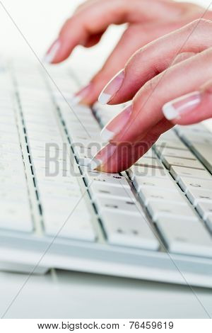 a woman in an office working on the keyboard of a computer