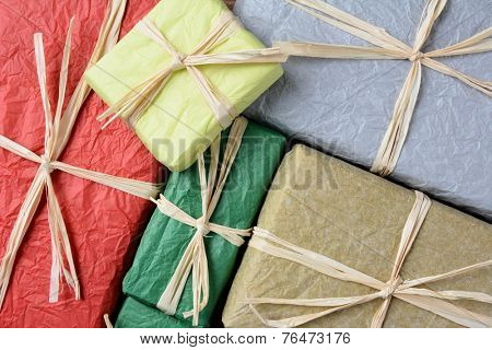 High angle closeup shot of a group of Christmas presents wrapped with colorful tissue paper. The gifts are tied with raffia. Horizontal format filling the frame.