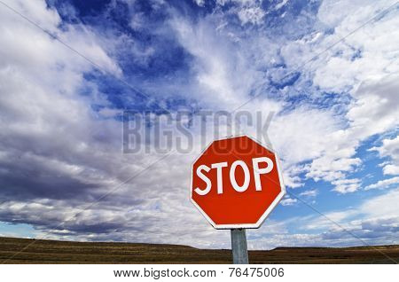 view of a stop signal with cloudy sky