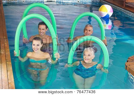 Smiling group doing aqua fitness class together in a swimming pool