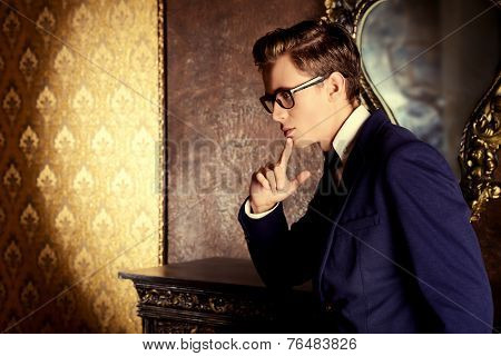Handsome respectable man in elegant suit stands in a room with classic vintage style. Business. Fashion. poster