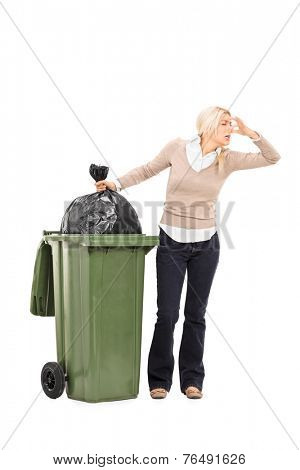 Full length portrait of a disgusted woman standing next to a trash can isolated on white background