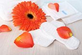 Sanitary pads, orange flower and rose petals on wooden table background poster