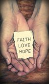 Faith Love Hope stone block in hands with dark background. poster