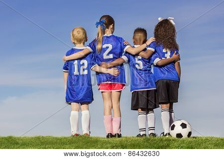 Diverse group of boys and girls soccer players standing together with a ball against a simple blue sky background