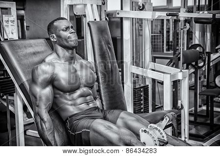 poster of Hunky muscular black bodybuilder working out in gym exercising legs on machine. Black and white shot