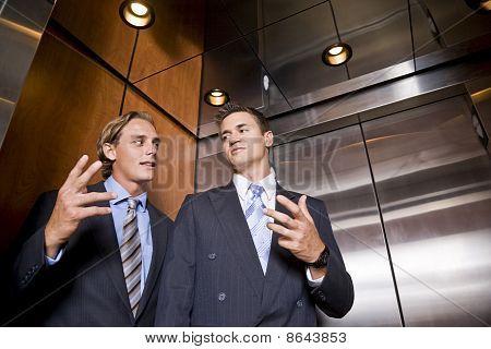 Businessmen Riding In Elevator Conversing