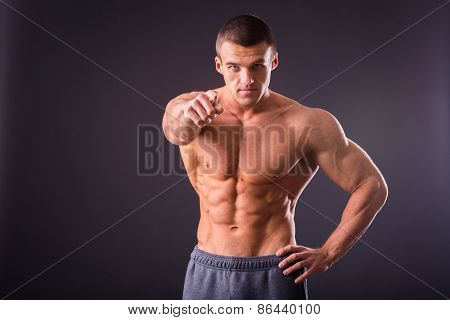 Young slim bodybuilder. Strong of a handsome muscular bodybuilder posing over black background. poster